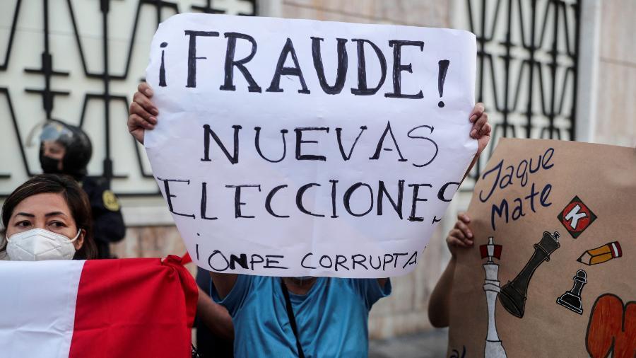 17.abr.2021 - Manifestantes seguram cartazes contra os candidatos presidenciais do Peru Pedro Castillo e Keiko Fujimori - Sebastian Castaneda/Reuters