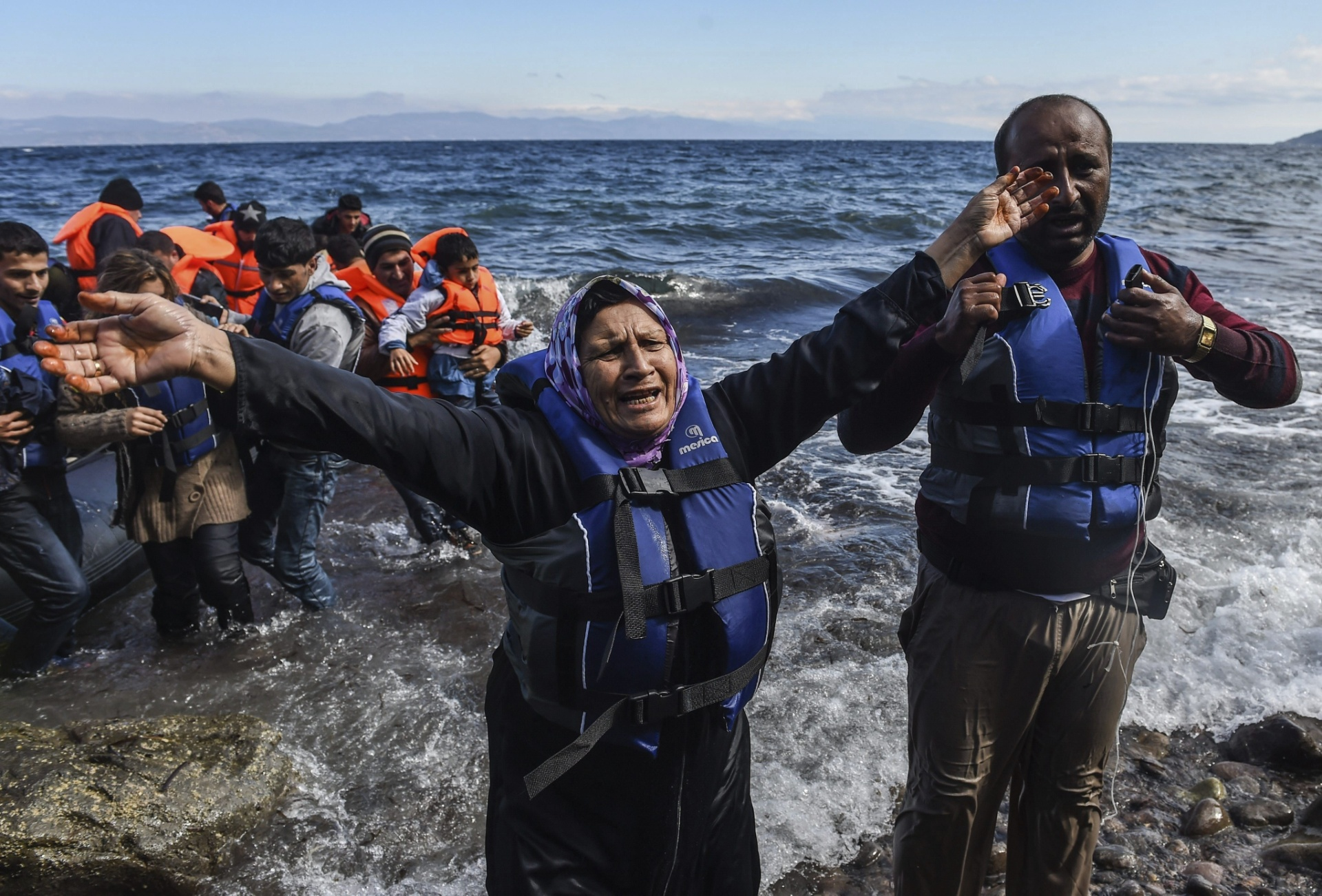 1º.out.2015 - Refugiada afegã comemora chegada à Ilha de Lesbos, na Grécia. Cerca de 100 mil refugiados já chegaram na ilha grega desde agosto, segundo a Guarda Costeira grega. O país é um dos principais destinos dos refugiados afegãos, paquistaneses e sírios que fogem de guerras e tentam uma nova vida na Europa