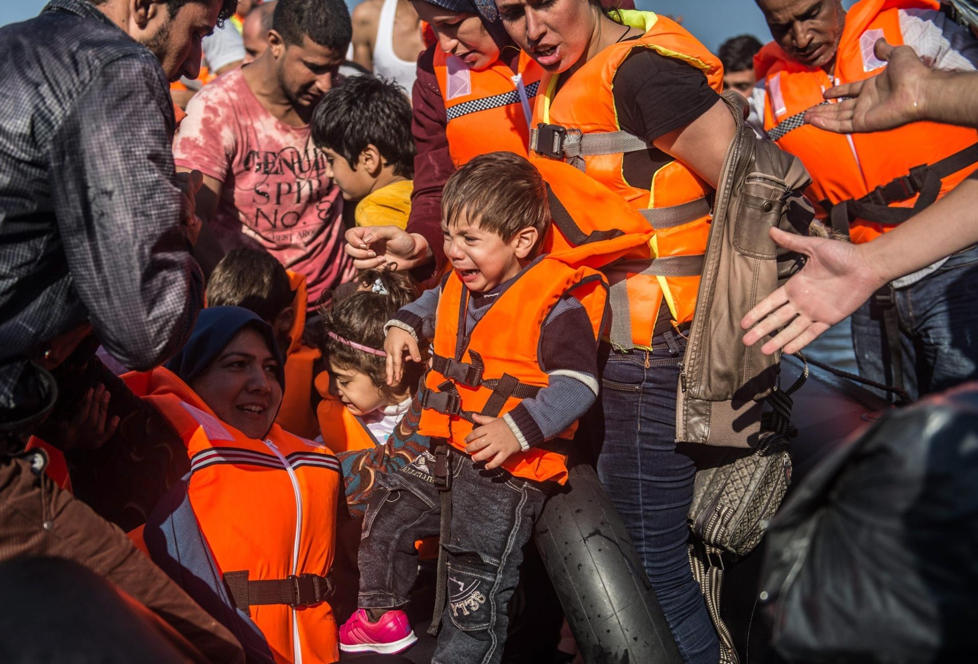 5.out.2015 - Criança síria chora enquanto é resgatada de bote inflável lotado perto da costa de Skala Sikaminias, na ilha de Lesbos, na Grécia. A terceira maior ilha grega já recebeu aproximadamente 90 mil refugiados vindos da Síria, Afeganistão e Iraque que tentam chegar à Europa fugindo de guerras