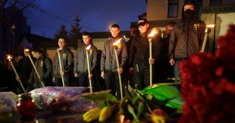 22.mar.2016 - Militares ucranianos seguram tochas em frente de coroas de flores que foram colocadas na embaixada belga em Kiev, na Ucrânia, após o atentado em que ao menos uma das três explosões foi provocada por um homem-bomba