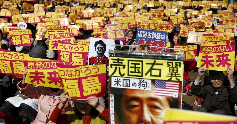 26.mar.2016 - Manifestantes exibem cartazes contra o uso da energia nuclear durante protesto em Tóquio, no Japão. Parte dos cartazes mostra a foto do primeiro-ministro do país, Shinzo Abe, criticado, dentre outras coisas, por seu apoio a interesses americanos na região