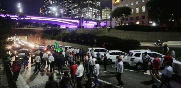 Motoristas de táxi fecham o corredor Norte-Sul, próximo ao túnel Anhangabaú e à Prefeitura de São Paulo, na noite de terça-feira (10)