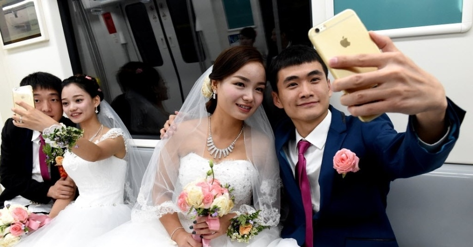 """9.ago.2016 - Recém-casados fazem """"selfies"""" no metrô em Zhengzhou, na província de Henan, na China. Uma cerimônia de casamento em grupo foi realizada para comemorar o Qixi Festival, ou Dia dos Namorados chinês"""