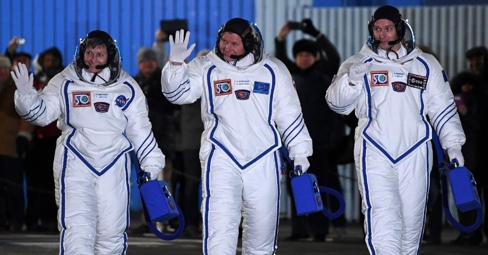 OS NOVOS HUMANOS NO ESPAÇO - Os astronautas Thomas Pesquet (à dir.), da França, Oleg Novitsky (ao centro), da Rússia, e Peggy Whitson (à esq,), dos Estados Unidos, acenam em Balkonur, no Cazaquistão, antes de embarcarem no foguete que os levará para a Estação Espacial Internacional. A equipe ficará cerca de quatro meses na estação conduzindo experimentos