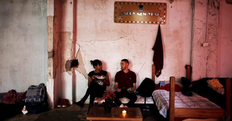 16.nov.2016 - Sentados em sofá improvisado, Fernanda (à esquerda), 20, e Aleksander (à direita), 23, comem dentro de prédio ocupado no Centro de São Paulo