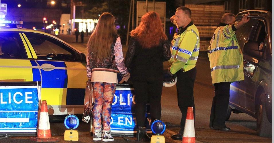22.mai.2017 - Policial orienta mãe e filha a deixarem o local logo após a explosão que ocorreu na Manchester Arena