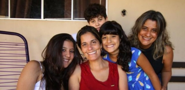 Thais Valadares ao meio, de vermelho, acompanhada da família
