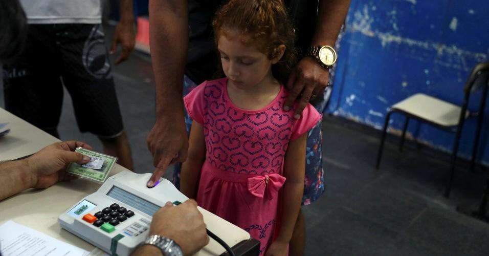 28.out.2018 - Criança acompanha pai durante votação no Rio de Janeiro