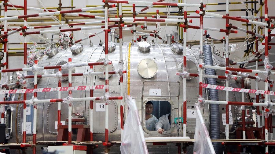 """Homem trabalha dentro de um reator de fusão nuclear HL-2M Tokamak, apelidado como o """"sol artificial"""", em construção em Chengdu, província de Sichuan, China - Liu Haiyun/Chengdu Economic Daily/Reuters"""