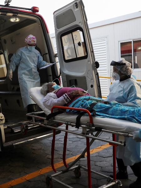 Profissionais de saúde transportam paciente com sintomas da covid-19 para ambulância - Amanda Perobelli