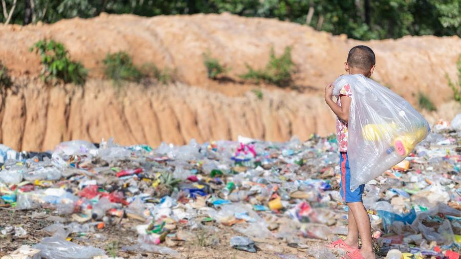 Menino pobre cata lixo no lixão, pobreza, trabalho infantil, exploração, criança trabalhando - iStock