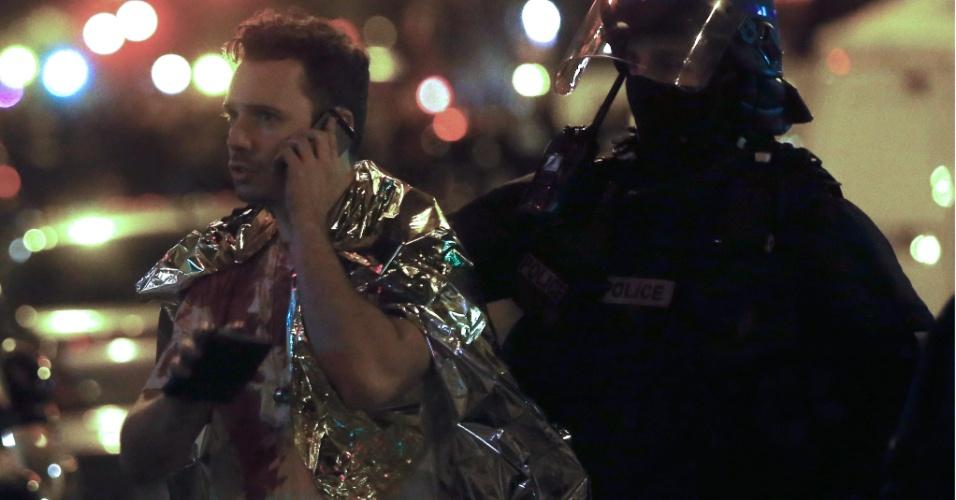 13.nov.2015 - Homem com camisa suja de sangue fala ao telefone próximo à sala de concertos Bataclan após tiroteio em Paris, na França. Tiroteios e explosões aconteceram na noite desta sexta-feira (13) em Paris. A polícia relatou ao menos duas explosões nas proximidades do estádio Stade de France, onde o presidente francês, François Hollande, acompanhava um amistoso da seleção francesa
