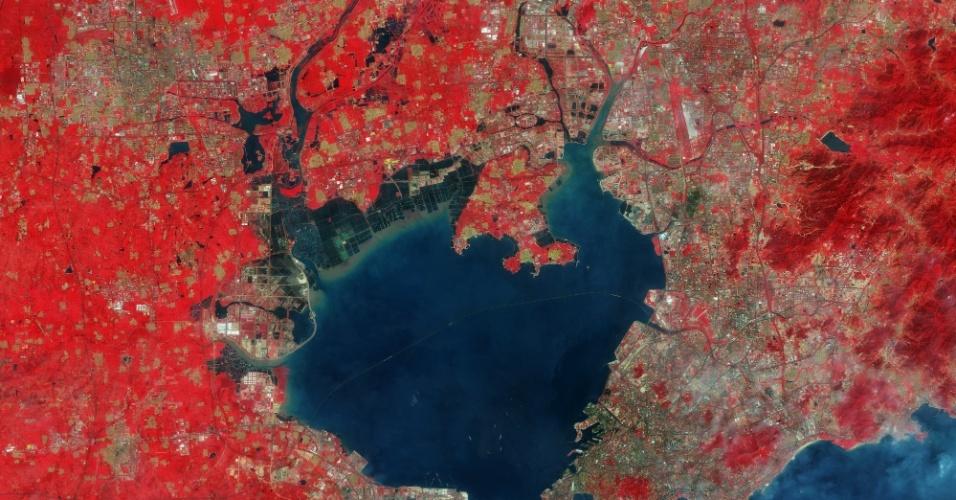 13.nov.2015 - Imagem capturada pelo satélite Sentinel-2A da ESA (Agência Espacial Europeia) mostra a cidade de Qingdao e seus arredores, na província de Shandong, leste da China. Devido ao instrumento de alta resolução multiespectrais do satélite, podemos distinguir claramente os barcos entrando e saindo da baía, junto com a impressionante ponte Jiaozhou Bay, de 26,7 km de comprimento, listada no Guinness como a mais longa a passar por cima da água. O Sentinel-2A  registra imagens de resolução de imagem para monitorização da Terra, cobrindo vegetação, solo e cobertura de água, vias navegáveis interiores e áreas costeiras