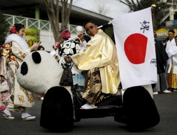 11.jan.2016 - Homem passeia em um veículo em forma de panda durante a celebração do Dia da Maioridade, em um parque de diversões em Tóquio, no Japão. De acordo com um anúncio do governo, mais de 1,2 milhões de homens e mulheres que nasceram em 1995 se tornaram maiores de idade, o que no país acontece ao completar 20 anos
