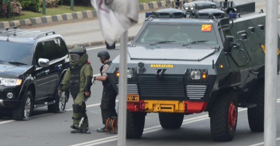 14.jan.2016 - Policial indonésio usa equipamento de proteção contra explosivos ao se aproximar de local atingido por bomba após uma série de explosões no centro de Jacarta