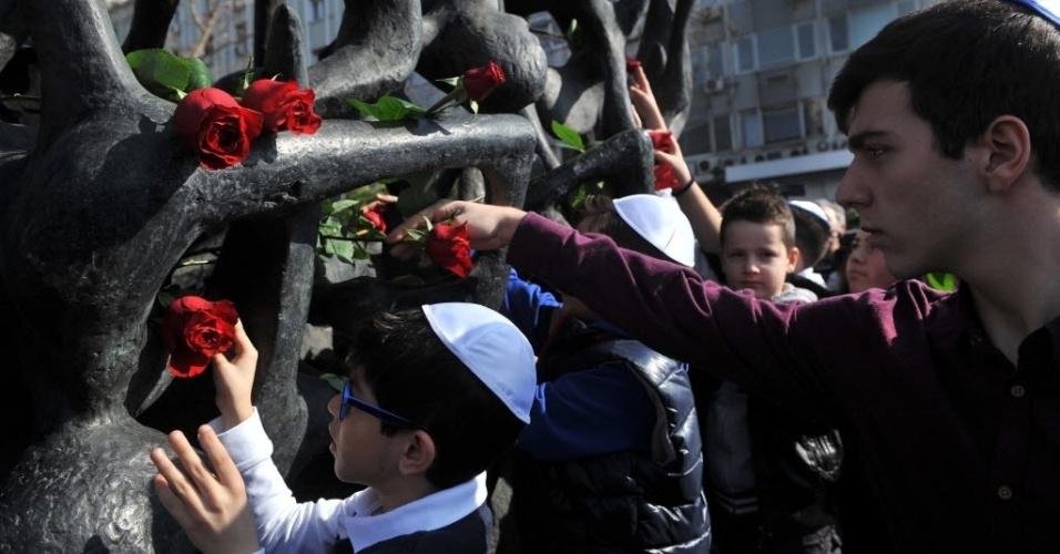 31.jan.2016 - Crianças e jovens depositam rosas no Memorial do Holocausto, em Tessalônica, Grécia, neste domingo (31). Uma cerimônia lembrou a perseguição dos judeus durante a Segunda Guerra Mundial. Dos 65 mil judeus gregos que foram vítimas do nazismo, 50 mil eram de Tessalônica. Oficialmente, a Grécia lembra o Holocausto no mês de janeiro