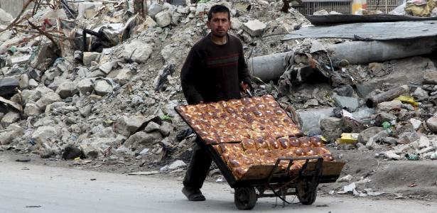Homem vendendo pão passa por destroços de bombardeios em Aleppo, na Síria