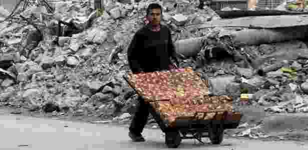 Homem vendendo pão passa por destroços de bombardeios em Aleppo, na Síria - Abdalrhman Ismail/Reuters