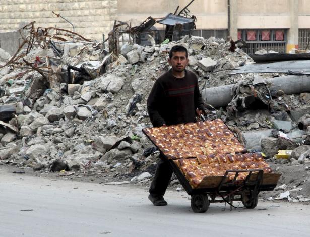 10.fev.2016 - Vendedor de pão passa por destroços de bombardeios em Aleppo, na Síria