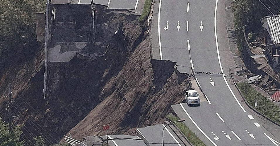 16.abr.2016 - Carro escapa por muito pouco de ser engolido por erosão em estrada de Kumamoto, no Japão. Destruição foi causada por terremoto de magnitude 7.3 na escala Richter, ocorrido na sexta-feira (19). Tremor matou ao menos 19 pessoas e deixou outras 760 hospitalizadas. Estima-se que ao menos 80 possam estar presas sob escombros