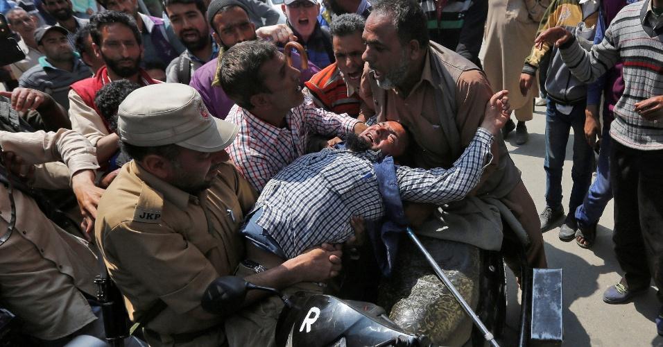 10.mai.2016 - Policial indiano detém manifestante durante protesto na cidade de Srinagar por aumento da pensão paga pelo governo a pessoas com deficiência