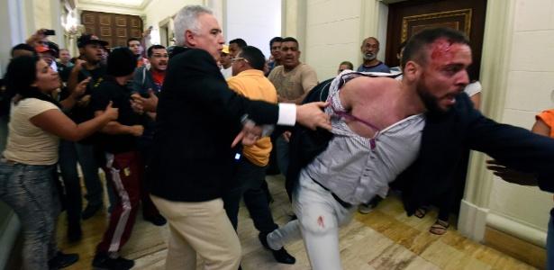 23.out.2016 - Deputado da oposição tenta passar entre manifestantes pró-governo para entrar em sessão extraordinária da Assembleia Nacional, em Caracas, na Venezuela