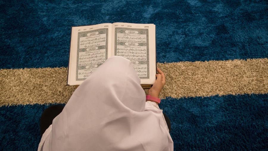 Mulher lê o livro sagrado no interior da Mesquita Brasil, em São Paulo, durante o Ramadã - Amanda Perobelli/UOL