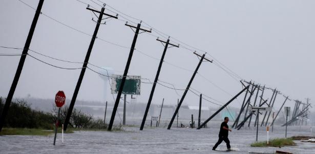 Homem caminha em área alagada após a passagem do furacão Harvey em Rockport, no Texas