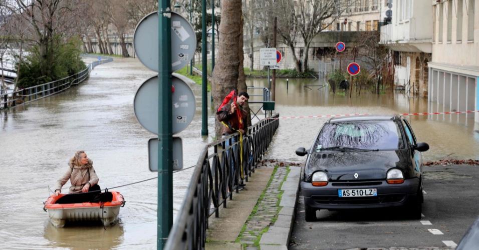 24.jan.2018 - Casal usa barco para se locomover nas margens inundadas do rio Sena, em Paris, França