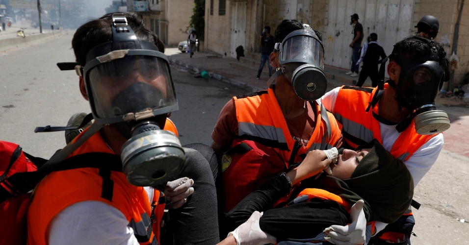 14.mai.2018 - Mulher palestina é resgatada durante conflito entre manifestantes palestinos e forças israelenses próximo a Ramallah, na Cisjordânia