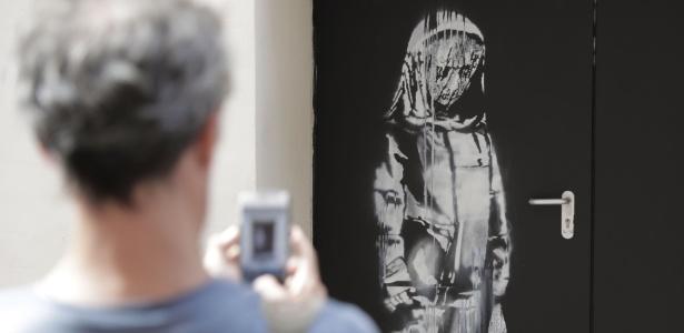Pintura de uma silhueta triste na porta da casa de shows parisiense Bataclan, onde houve um atentado em 2015 - Thomas Samson/AFP Photo