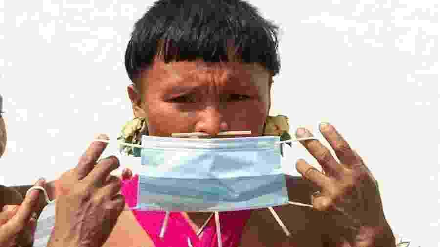 Yanomami veste máscara de proteção em Alto Alegre (RR). População indígena ameaçada gerou acusações ao Brasil durante a ditadura militar - Joédson Alves/EDE