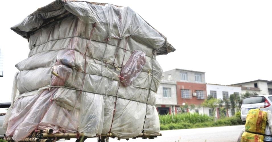 24.mai.2013 - Liu Lingchao, 38, carrega sua casa improvisada por rua de Shapu, na cidade de Liuzhou, região autônoma de Guangxi Zhuang (China), em foto divulgada nesta sexta-feira (24). Cinco anos atrás, Liu decidiu voltar para sua cidade natal e, para isso, construiu com bambu, sacolas plásticas e lençóis uma casa portátil de 1,5 metros de largura, dois metros de altura e 60 kg, que ele carrega por 20 km por dia. Para se sustentar, ele coleta lixo. Lui está a cerca de 30 km da cidade onde nasceu