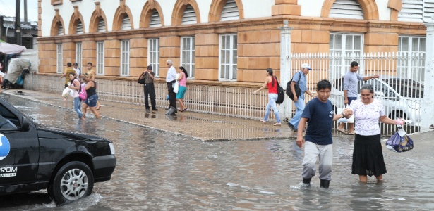 Pedestres enfrentam alagamento no centro de Manaus, no Amazonas, após o transbordamento de galerias subterrâneas. O prefeito da cidade, Artur Neto, decretou situação de emergência devido à cheia de rios