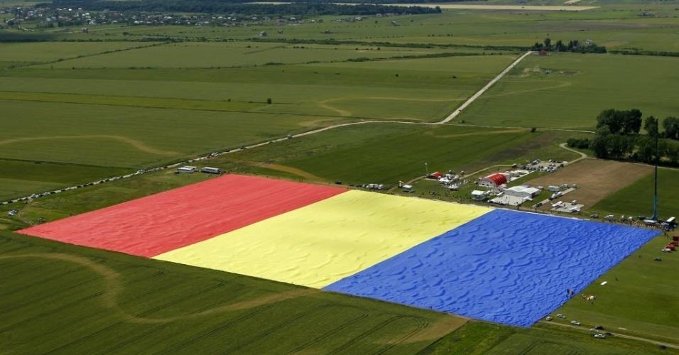 27.mai.2013 - Em imagem aérea, bandeira gigante da Romênia desfraldada em Bucareste, nesta segunda-feira (27). A Romênia entrou para o livro dos recordes com a criação da maior bandeira já existente. Duzentas pessoas tiveram que ajudar a abrir a peça de duas toneladas, medindo 349 por 226 metros - cerca de três campos de futebol