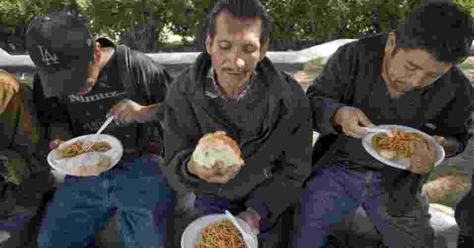 7.mai.2013 - José Ruiz (centro), 47, come prato de macarronada em albergue para indigentes em La Roca del Alfarero, em Tijuana, no noroeste do México. Ele, que viveu durante trinta anos ilegalmente em Los Angeles, nos Estados Unidos, e centenas de outros mexicanos vivem no albergue desde fevereiro, depois de terem sido expulsos do país. Centenas de pessoas deportadas pelos Estados Unidos vivem em más condições na fronteira. O aumento do controle de segurança na fronteira entre os EUA e o México e o maior número de deportações de imigrantes mexicanos tem provocado alta no número de indigentes nas cidades fronteiriças mexicanas - David Mung/EFE