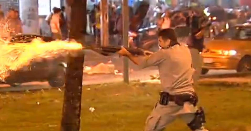 28.mai.2013 - Policial atira contra estudantes durante protesto contra o aumento da tarifa do transporte coletivo de Goiânia na praça da Bíblia, no Setor Leste Universitário, na capital de Goiás. Com o acréscimo de 11%, a passagem passou de R$ 2,70 para R$ 3