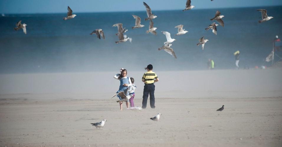 26.mai.2013 - Gaivotas voam sobre crianças em na praia de Coney Island, em Nova York (EUA). Sete meses após a tempestade Sandy, as praias da cidade foram reabertas para o público no Memorial Day, feriado comemorado na última segunda-feira (29) que lembra militares americanos mortos em guerras