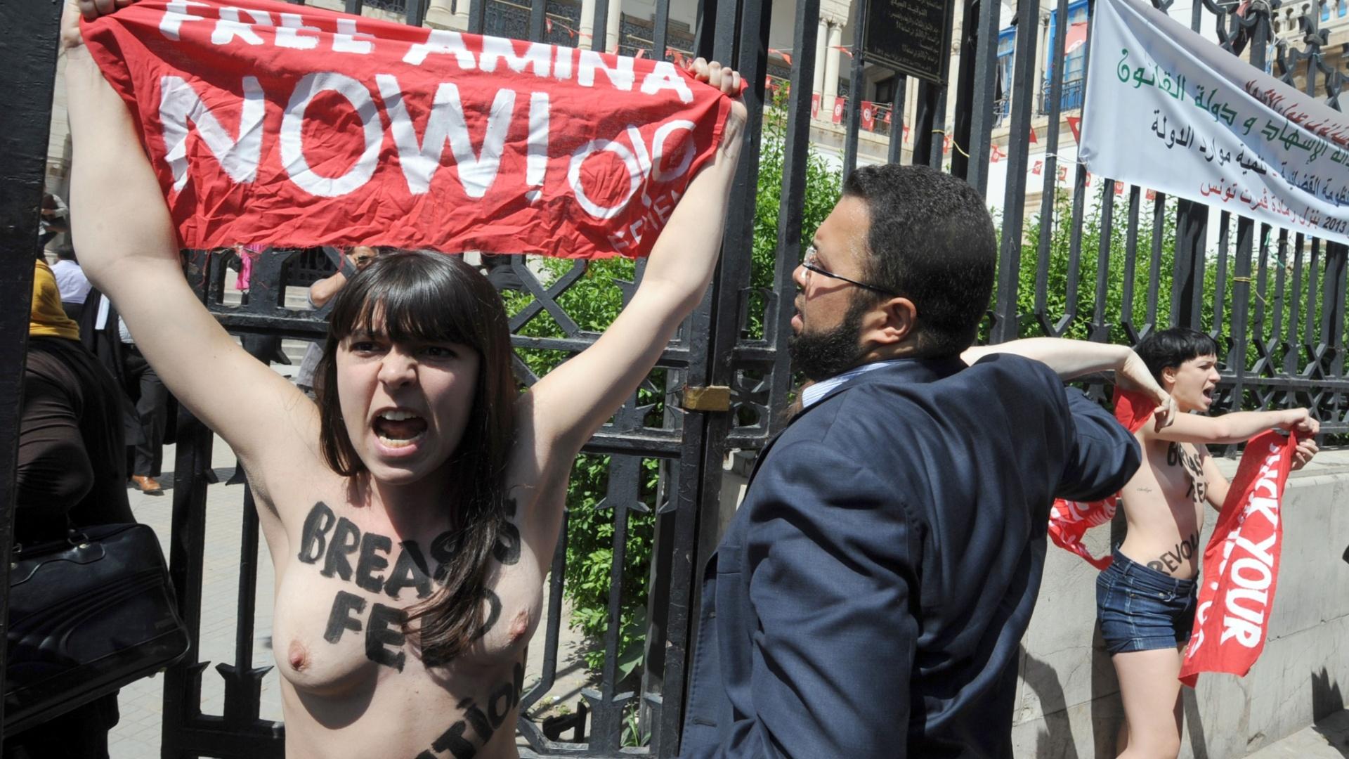 29.mai.2013 - Advogado tenta conter manifestante do Grupo Femen, que protestou em frente ao Palácio da Justiça em Túnis, capital da Tunísia. Duas francesas e uma alemã exibiram faixas com os dizeres