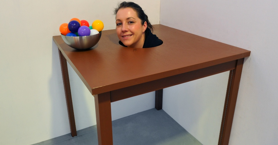 """29.mai.2013 - Exposição em Dresden, na Alemanha brinca com a ilusão de ótica. Nesta peça, mulher coloca a cabeça em um buraco na mesa e seu corpo desaparece com um truque de espelhos. A exposição interativa chamada """"Wanderings about the Senses"""" vai até 10 de junho de 2013"""