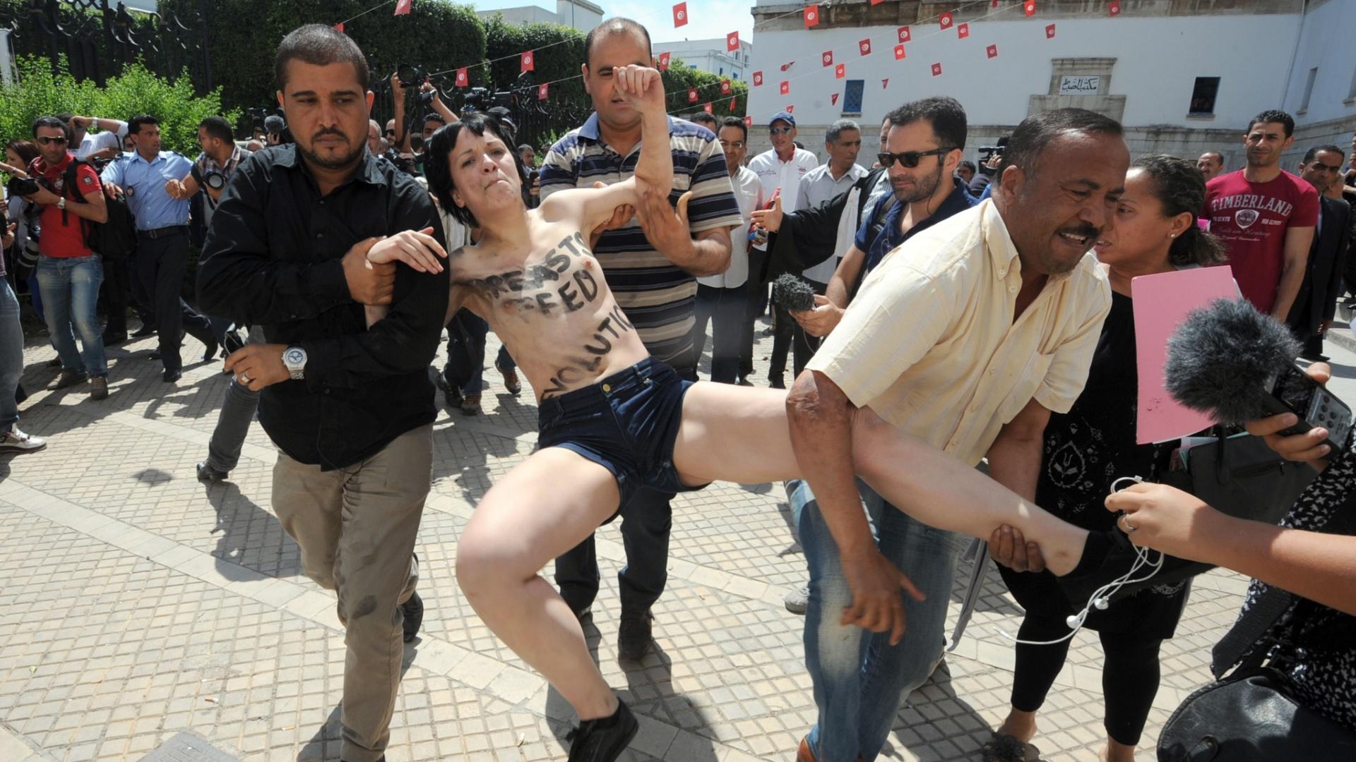29.mai.2013 - Manifestante do Grupo Femen, que protestou em frente ao Palácio da Justiça em Túnis, capital da Tunísia, é presa. Duas francesas e uma alemã exibiram faixas com os dizeres