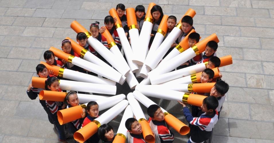 30.mai.2013 - Estudantes chineses posam com cigarro durante campanha do Dia Mundial Sem Tabaco, nesta quinta-feira (30), em Handan, na China