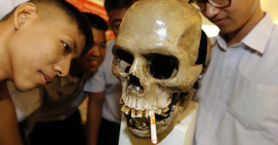 30.mai.2013 - Estudantes tailandeses observam caveira com cigarro durante campanha do Dia Mundial Sem Tabaco, nesta quinta-feira (30), em Bangkok, na Tailândia