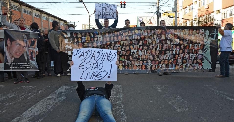 30.mai.2013 - Manifestante deita no chão durante ato realizado em Santa Maria (RS) em repúdio à decisão do Tribunal de Justiça do Rio Grande do Sul que determinou a soltura de quatro réus da tragédia na boate Kiss --eles deixaram o presídio na noite de quarta-feira (29)