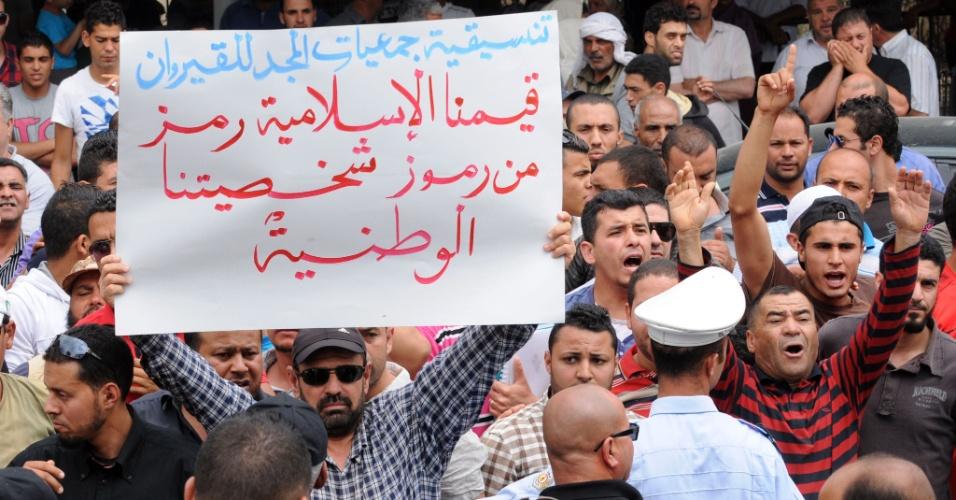 30.mai.2013 - Manifestantes tunisianos seguram cartazes em frente ao Tribunal de Bruxelas elogiando os valores islâmicos e defendendo a condenação de Amina Tyler, integrante do grupo feminista Femen, presa na Tunísia. Ela começou a ser julgada nesta quinta-feira (30) por posse de um spray de autodefesa, em Bruxelas. Três europeias do grupo feminista que na véspera realizaram um protesto em Túnis com os seios à mostra para apoiá-la, na primeira ação deste tipo em um país árabe, serão conduzidas ao Ministério Público da capital. O grupo de tunisianos também protesta contra a ação das ativistas