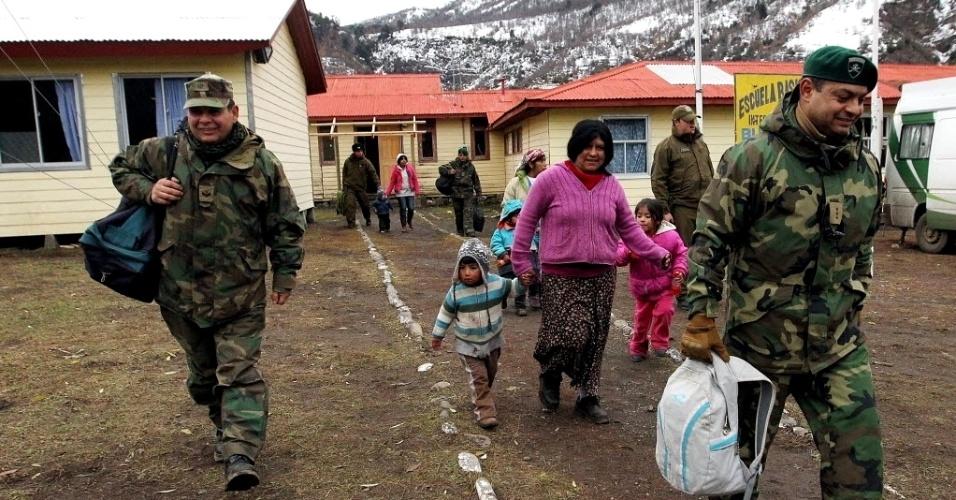 30.mai.2013 - Militares ajudam famílias a evacuar encostas do vulcão Copahue, na fronteira entre a Argentina e Chile, na região do Bio Bio, a 650 km ao sul de Santiago. As autoridades locais emitiram alerta vermelho na área por risco de erupção