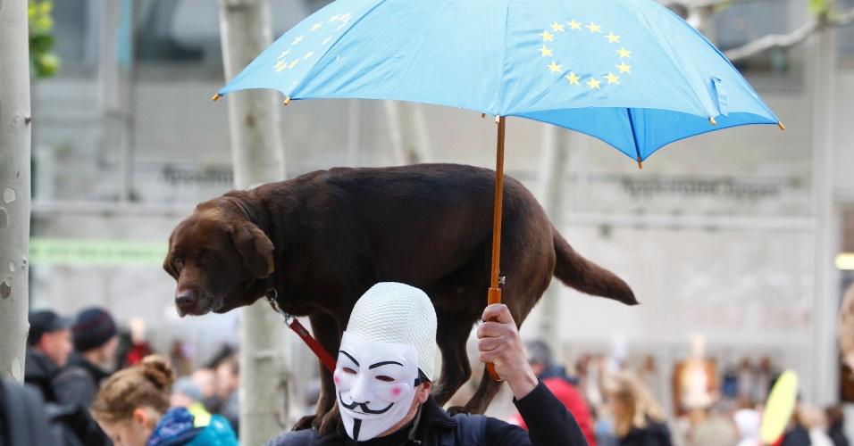 """31.mai.2013 - Manifestante leva cachorro em protesto em frente a sede do Banco Central Europeu, em Frankfurt (Alemanha). Chamado ?Blockupy? -- jogo de palavras que une os termos bloquear e ocupar, e é inspirado no movimento """"Ocupe Wall Street"""", ocorrido em 2011 nos Estados Unidos -- o protesto é contrário as medidas de austeridade econômica da zona do euro, liderada pela Alemanha, que, entre outras questões, teria causado o endividamento de nações do sul da Europa"""