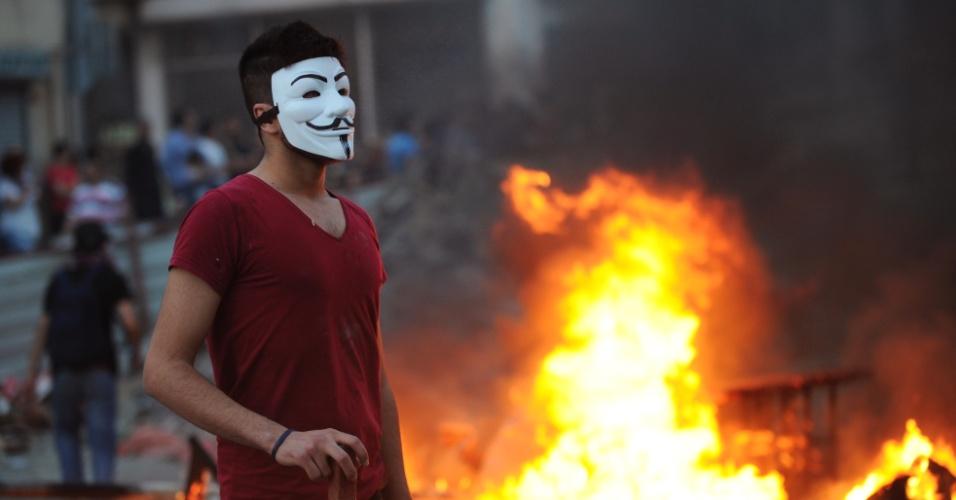 """31.mai.2013 - Manifestante usa máscara popularizada no filme """"V de Vingança"""", que ficou popular em protestos pelo mundo, durante confronto com a polícia turca contra a construção de centro comercial na Praça Taksim, em Istambul, Turquia"""