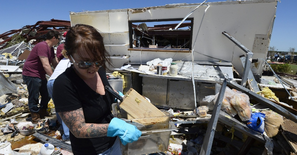 1º.jun.2013 - Sara Scarritt (foto) tenta recolher o que sobrou após passagem de tornado na região de El Reno, em Oklahoma (Estados Unidos). Segundo as autoridades locais, pelo menos nove pessoas morreram após a passagem do tornado. A tempestade está indo em direção leste nas proximidades do Estado do Missouri