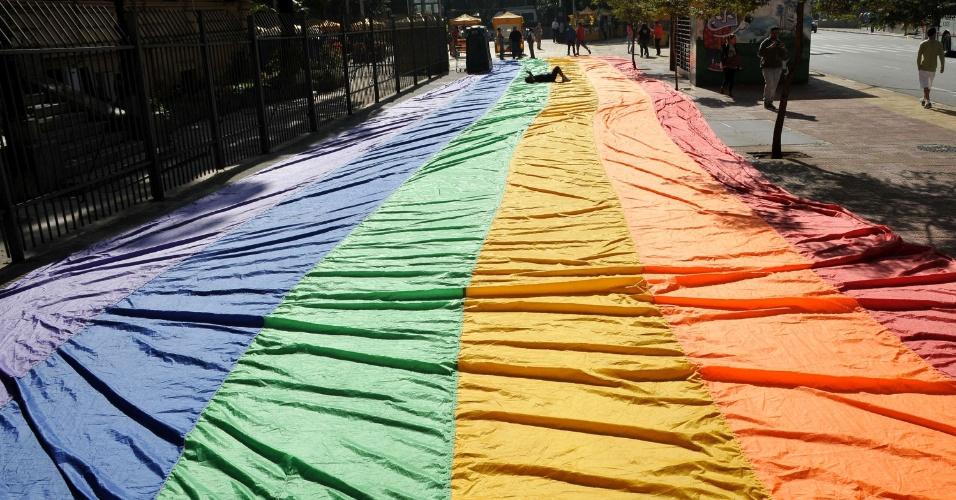 1º.jun.2013 - A bandeira oficial da Parada Gay, que é estendida durante o desfile realizado anualmente na avenida Paulista, em São Paulo, foi lavada por funcionários da APOGLBT, associação que organiza a parada, e aberta para secar ao sol na calçada da praça da República, centro da capital paulista, neste sábado (1º). O bandeirão com cerca de 20 metros de comprimento e representando as cores do arco-íris simboliza o orgulho gay, chamando a atenção de quem passava pelo local